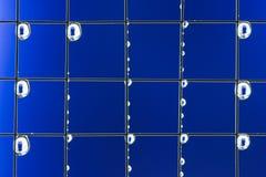 Metal Ineinander greifen mit Wassertropfen auf dem blauen Hintergrund Lizenzfreie Stockfotos