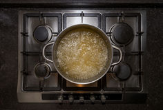 Metal iron aluminum pan on traditional stove cooker boiling water Stock Photography
