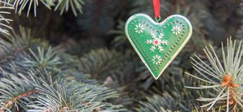 Metal iron decor heart with rustic ornaments. Concept for winter, Christmas, New Year, pine tree decoration. Front view. Closeup. Web banner stock photo