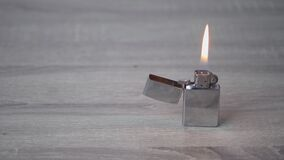 Metal iron gasoline lighter burns and stands on a light wooden table