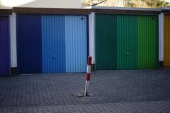 Tiered garages. A metal and iron green and blue garage door lined up garages stock photos