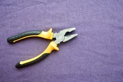 Metal, iron pliers with rubberized yellow-black handles Royalty Free Stock Photos