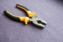 Metal, iron pliers with rubberized yellow-black handles Royalty Free Stock Images