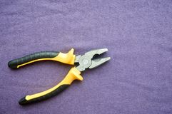 Metal, iron pliers with rubberized yellow-black handles Royalty Free Stock Photography