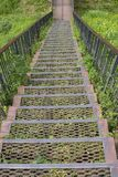 Metal iron staircase leading down. Metal steps iron railings, descending from a green grassy hill. Old rusty iron staircase stock photos