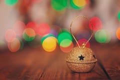 Metal Jingle Bell con la estrella en la tabla de madera Decorati de la Navidad Imagen de archivo