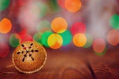 Metal Jingle Bell del oro con el copo de nieve en copia de madera de la tabla Fotografía de archivo