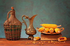 Metal jug, corn, and books Royalty Free Stock Images