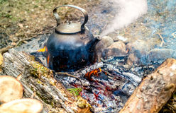 Metal kettle boiling on the fire. Metal pot is on the coals of a fire and boils Stock Photo