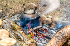Metal kettle boiling on the fire. Metal pot is on the coals of a fire and boils Stock Image