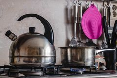 Metal Kettle and pot on a burning gas stove stock images