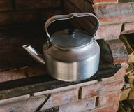A metal kettle on a red brick stove. In the winter, hot water is boiled in the pot over traditional stove. This old kettle is used in a cabin which is fueled Stock Photography