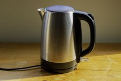 A metal kettle on wood. stock photography
