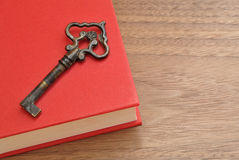 Metal key on a red book. Metal key and a red book on a wooden top Royalty Free Illustration