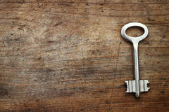 Metal key on wooden background Stock Images