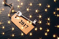 Metal key with 2017 year tag. Festive picture with lightening golden stars Royalty Free Stock Photo