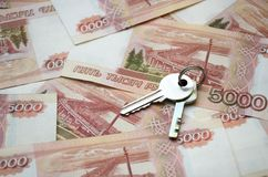 Metal keys on a horizontal background of a variety of banknotes of five thousand Russian rubles royalty free stock image