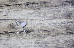 Metal keys and a steel open lock on a wooden boards. Stock Photo