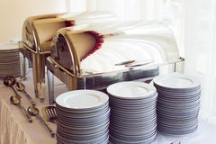Metal kitchen equipments and plates on the table for fine wedding dining or another catered event Stock Photography