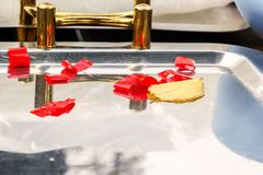 Metal kitchen tray with yellow handles adorned with red ribbons with a fallen yellow autumn leaf. Designer workpiece. Copy space royalty free stock photography