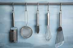 Metal kitchen utensils hanging on rack. Against color wall royalty free stock photo