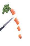 Metal knife cuts carrots on the fly. Carrots and knife. Metal knife cuts carrots. Metal knife cuts carrots on the fly Stock Photos