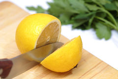 Metal knife cuts lemon. Metal knife cuts the lemon and herbs, board Royalty Free Stock Photo