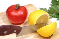 Metal knife cuts lemon, tomato. Metal knife cuts the lemon and herbs, board, tomato. The process of cooking Stock Photos