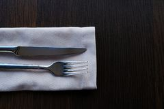 Metal knife and fork on a light napkin on a wooden table. Clean Cutlery for food. royalty free stock images