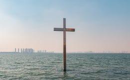 Metal l'incrocio cristiano nell'acqua sopra il fondo del cielo blu fotografia stock libera da diritti