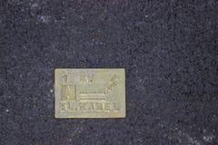 Metal l'indicatore sull'asfalto - cavi ad alta tensione qui sotto Immagine Stock