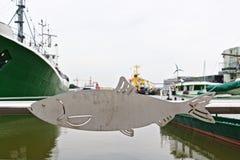 Metal l'inferriata con l'ornamento a forma di pesce e harbor la vista nei precedenti sparati da una strada pubblica, nessuna prop Immagine Stock