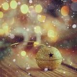 Metal l'or Jingle Bell avec l'étoile sur le Tableau en bois Image stock