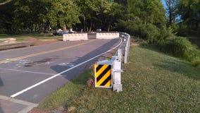 Metal la barrière protectrice avec le signe noir et jaune réfléchi d'inscription au petit pont nouvellement construit 2-C-504 NJ, Photo libre de droits