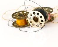 Metal la bobine des bobines de fil ou de machine à coudre d'isolement sur le petit morceau Photo libre de droits