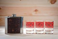 Metal la boccetta per le bevande alcoliche e tre vetri su un fondo di legno Fotografia Stock Libera da Diritti