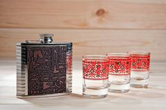 Metal la boccetta per le bevande alcoliche e tre vetri su un fondo di legno Fotografie Stock Libere da Diritti