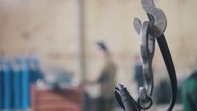 Metal la cadena del gancho en el fondo de trabajadores en la fábrica almacen de metraje de vídeo