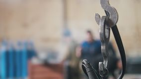 Metal la cadena del gancho en el fondo de trabajadores en la fábrica Foco en encadenamiento almacen de video