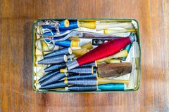 Metal la caja de almacenamiento con los hilos y los accesorios de costura de la costura en el fondo de madera Imagenes de archivo