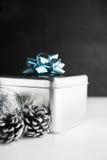 Metal la caja de regalo con el arco azul y las chucherías de Navidad en los fondos de madera blancos y negros Imagenes de archivo