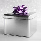 Metal la caja de regalo con el arco púrpura en el fondo blanco del brillo Imagen de archivo libre de regalías