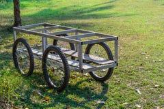 Metal la carretilla y el piso de madera con cuatro ruedas Imagen de archivo