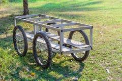 Metal la carretilla y el piso de madera con cuatro ruedas Fotografía de archivo