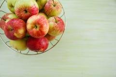 Metal la ciotola con le mele verdi, gialle e rosse sui precedenti di legno verdi e bianchi Immagine Stock