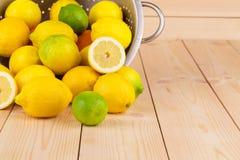 Metal la colapasta in pieno della tavola di legno dei limoni o Immagine Stock
