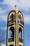 Metal la cruz en el tejado de un campanario amarillo antiguo Fotografía de archivo
