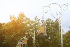 Metal la fila della posta della lampada nel parco con luce calda Fotografie Stock Libere da Diritti