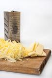 Metal la grattugia con formaggio tagliato sul bordo di legno Immagine Stock Libera da Diritti