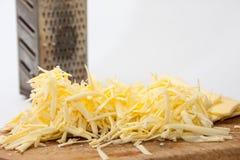 Metal la grattugia con formaggio tagliato sul bordo di legno Immagini Stock